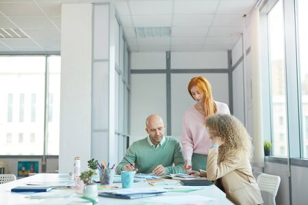 Group of three business people discussing documents while working at table in office, copy space