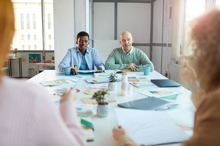 Portrait of two business women sitting opposite two men while negotiating deal in office, copy space Reklamní fotografie