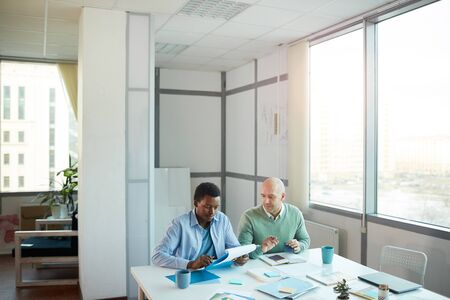 Wide angle view of African-American young man consulting with mature manager while sitting at table in office, copy space Reklamní fotografie