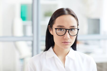 Head and shoulders portrait of young Asian businesswoman wearing glasses and looking at camera while posing in modern white office, copy space Reklamní fotografie