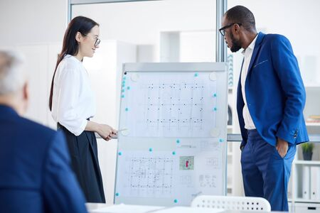 Portrait of young Asian businesswoman standing by whiteboard while presenting design project to boss during meeting in office, copy pace