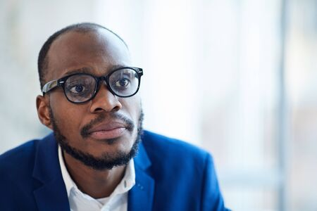 Head and shoulders portrait of successful African-American businessman wearing glasses looking at partner across table during meeting, copy space