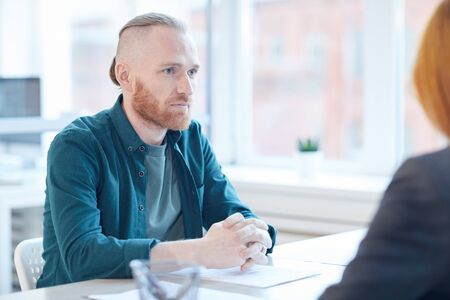 Portrait of contemporary bearded man listening to HR manager during job interview in office, copy space