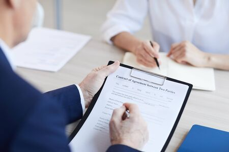 Close up of unrecognizable senior businessman signing contract agreement during meeting in office, copy space Foto de archivo