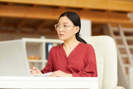 Portrait of successful Asian woman wearing red blouse working at desk in modern white office, copy space
