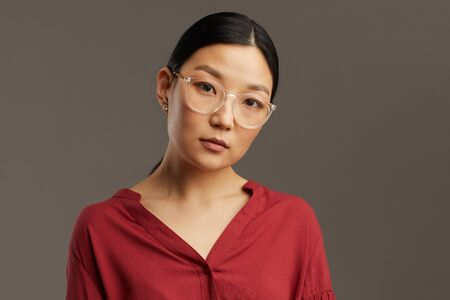 Head and shoulders portrait of elegant Asian woman wearing glasses and looking at camera while standing against grey background in studio, copy space Reklamní fotografie
