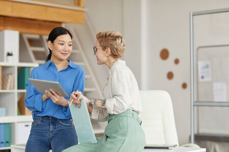 Waist up portrait of two modern businesswomen chatting cheerfully while enjoying work in office, copy space