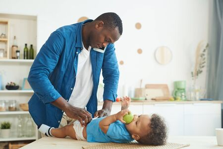 Side view portrait of mature African-American man calling wife while changing diaper to baby in home interior, copy space