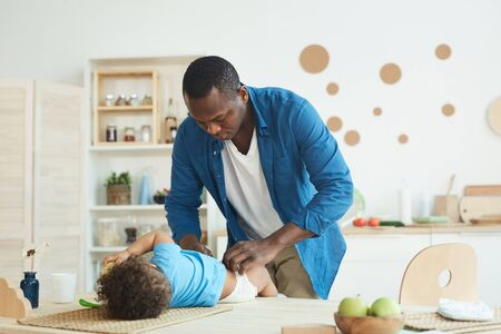 Portrait of African-American man changing diaper while caring for toddler at home, copy space