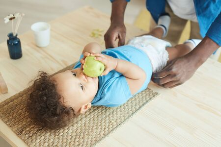 High angle view at unrecognizable father changing diaper to cute African-American toddler eating apple, copy space