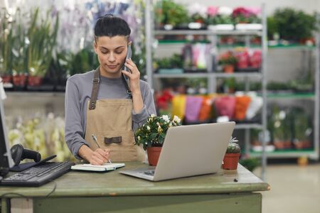Waist up portrait of female small business owner speaking by smartphone while standing behind counter in flower shop, copy space
