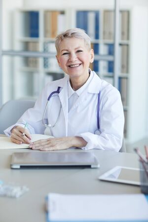 Portrait of mature female doctor smiling at camera while sitting at workplace in clinic interior