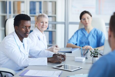 Portrait of young African-American doctor listening to colleague committee during medical conference, copy space