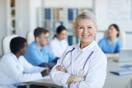 Waist up portrait of senior female doctor standing with arms crossed and smiling at camera against medical conference background, copy space