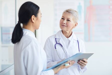 Waist up portrait of mature female doctor talking to trainee while standing in medical office interior, copy space Stockfoto