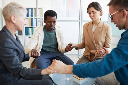 Multi-ethnic group of people holding hands in prayer while sitting in circle in support group, copy space Imagens