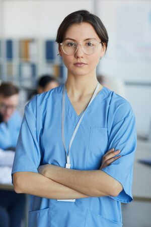 Waist up portrait of young nurse wearing glasses standing with arms crossed and looking at camera against medical conference background