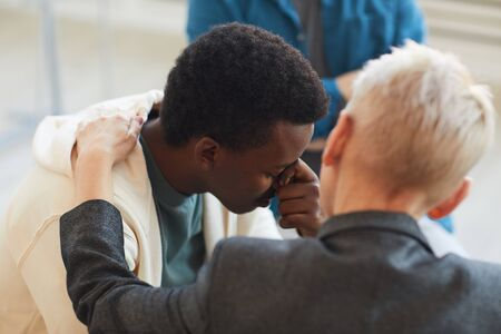 High angle view at young African-American man crying while sitting on chair on support group circle, copy space