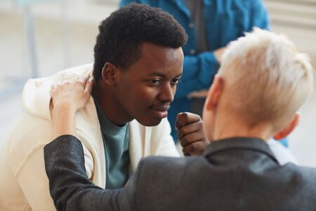 High angle view at young African-American man smiling gratefully to psychologist while while in support group circle, copy space