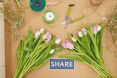 Top view at Spring theme composition with pastel pink tulips on wooden table and SHARE sign in flower shop