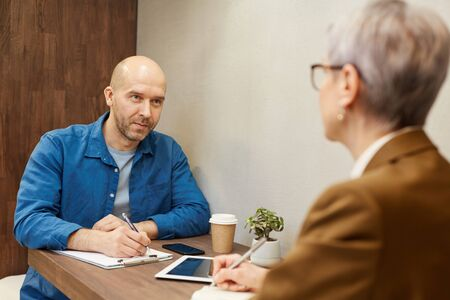 Portrait of mature bald man writing on clipboard while discussing contract with business manager during meeting at cafe table, copy space