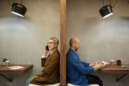 Minimal side view portrait of two adult people separated by wall while sitting in separate cafe booths, copy space