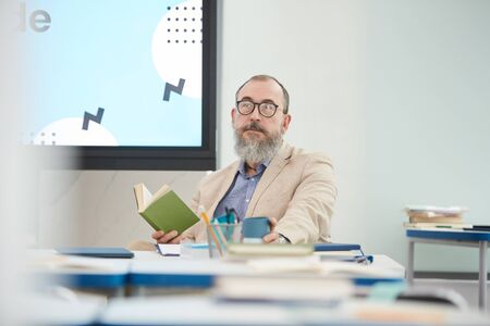 Portrait of senior bearded professor sitting at desk in school classroom and looking at camera, copy space Stock Photo