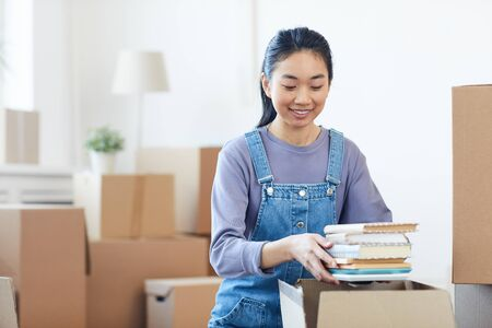 Portrait of young Asian woman packing books to cardboard boxes and smiling happily excited for moving to new house or dorm, copy space Standard-Bild