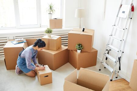Wide angle background of young Asian woman packing cardboard boxes in empty white room, moving, relocation and house decor concept, copy space Stock fotó