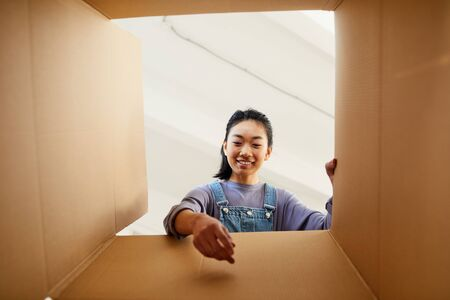 Low angle view at smiling Asian woman reaching into cardboard box while packing or unpacking for new home, copy space