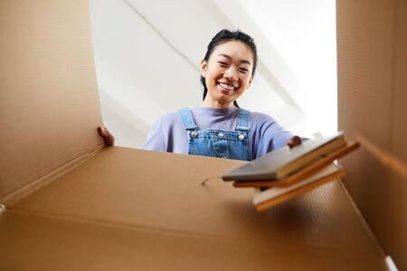 Low angle view at young Asian woman looking into cardboard box and smiling happily while packing or unpacking for new home, copy space 版權商用圖片 - 143940612