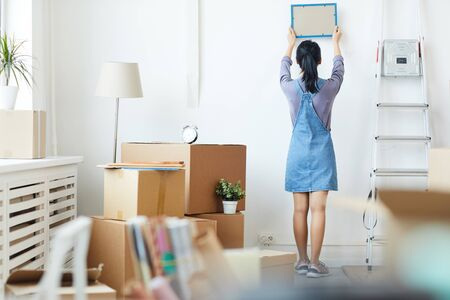 Full length back view portrait of young Asian woman decorating new home while moving in to new house or apartment, copy space