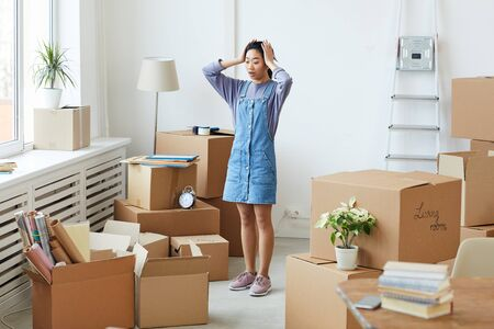 Full length portrait of frustrated Asian woman panicking while standing among cardboard boxes in empty room, house moving or relocation concept, copy space Standard-Bild