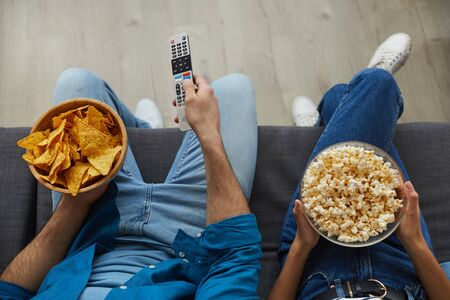 Top view close up of unrecognizable couple watching TV together while sitting on cozy sofa at home and enjoying snacks, copy space