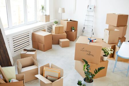 Wide angle background image of stacked cardboard boxes in empty room, moving, relocation and house decor concept, copy space Standard-Bild