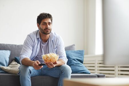 Portrait of mature bearded man watching TV and holding bowl of popcorn while sitting on sofa at home, copy space