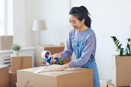 Portrait of smiling Asian woman packing cardboard boxes with tape dispenser while st moving out to new house, copy space