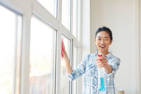 Portrait de taille d'une jeune femme asiatique pointant un pistolet de pulvérisation vers la caméra tout en lavant les vitres et en profitant du nettoyage de printemps, espace de copie