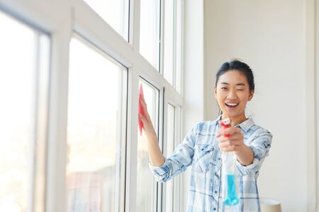 Waist up portrait of young Asian woman pointing spray gun at camera while washing windows and enjoying Spring cleaning, copy space