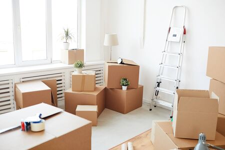 Wide angle background of stacked cardboard boxes in empty white room, moving, relocation and house decor concept, copy space 스톡 콘텐츠