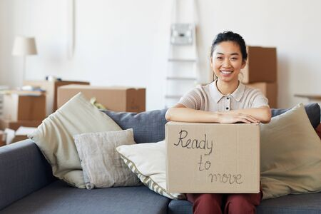 Portrait of young Asian woman holding cardboard box with ready to move inscription and smiling looking at camera, copy space Standard-Bild