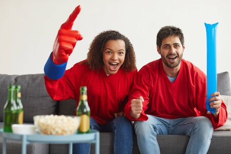 Portrait of modern mixed-race couple watching sports match on TV at home and cheering emotionally while wearing red team uniforms, copy space