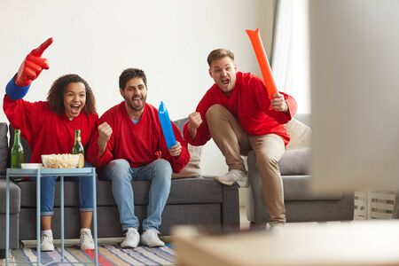 Full length view at group of friends watching sports match on TV at home and cheering emotionally while wearing red team uniforms, copy space