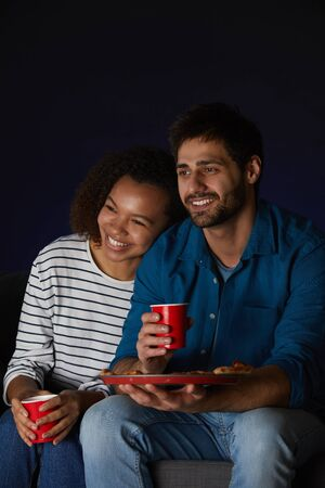 Vertical portrait of mixed-race young couple watching movies at home while eating snacks and popcorn sitting on sofa in dark room