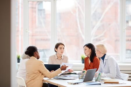 Wide angle view at diverse female business team discussing project while sitting at table during meeting in conference room, copy space