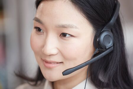 Head and shoulders portrait of smiling Asian woman wearing headset and talking to customer while working in call center or support service, copy space