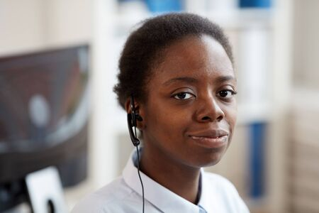 Head and shoulders portrait of smiling African-American woman wearing headset and looking at camera while working in support service call center, copy space