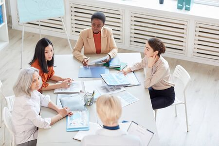 High angle view at diverse group of successful businesswomen discussing project while sitting at table during meeting in modern white office, copy space Archivio Fotografico