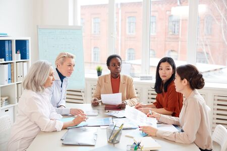 Multi-ethnic group of successful businesswomen discussing project while sitting at table against window during meeting in conference room, copy space Archivio Fotografico