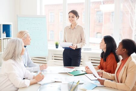 Portrait of smiling female manager presenting project plan to group of colleagues while standing by whiteboard during meeting in conference room, copy space